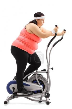 overweight woman exercising on a cross trainer machine