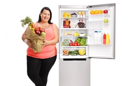 Overweight woman with bag of groceries leaning on refrigerator