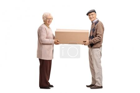 Elderly man and woman holding cardboard box