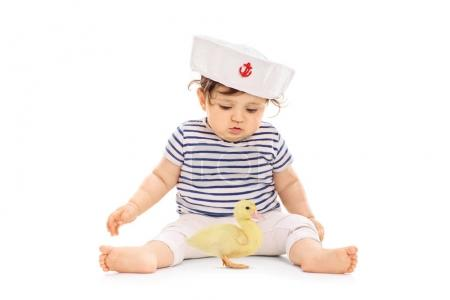 Baby girl in a sailor outfit with a small duckling