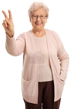 Joyful elderly woman making a victory sign