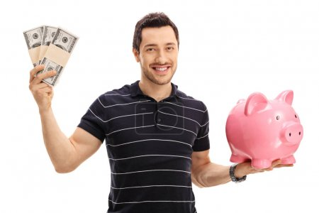 Photo for Young man holding bundles of money and a piggybank isolated on white background - Royalty Free Image