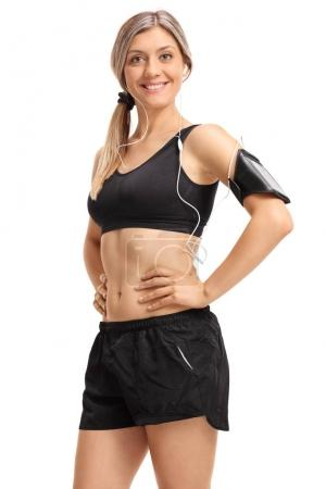 Photo for Fitness woman with an armband and earphones looking at the camera and smiling isolated on white background - Royalty Free Image