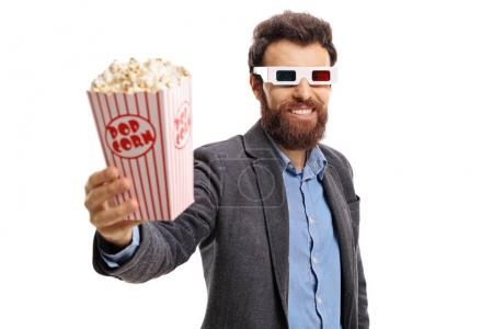 Photo for Bearded guy wearing 3D glasses and giving popcorn isolated on white background - Royalty Free Image