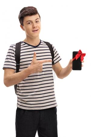 Photo for Teenage student showing a phone with a red ribbon and pointing isolated on white background - Royalty Free Image