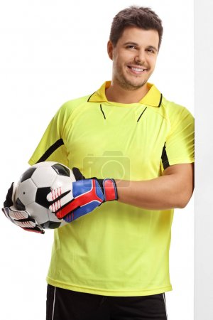 Goalkeeper with a football leaning against a wall