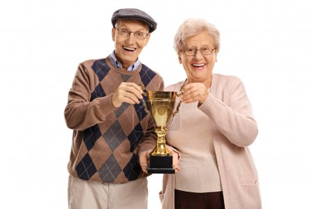 Elderly man and woman holding a golden trophy
