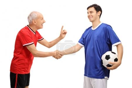 Old and young soccer players shaking hands