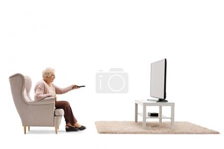 Photo for Elderly woman seated in an armchair watching television and changing channels isolated on white background - Royalty Free Image