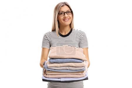 Frau mit einem Stapel gebügelter und gepackter Kleidung