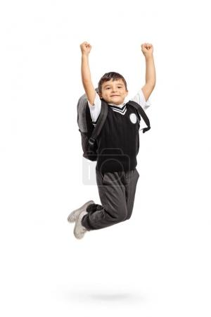 Overjoyed schoolboy jumping and gesturing happiness