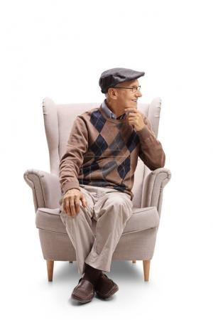 man sitting in an armchair and looking away