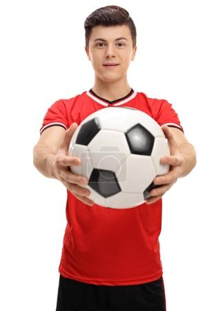Teenage soccer player giving a football