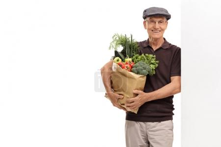 man holding a paper bag filled with groceries