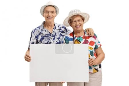 Elderly tourists holding a blank signboard