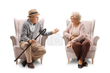 Elderly man and woman in armchairs talking