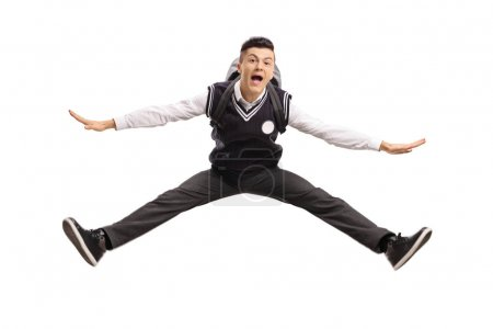 Overjoyed teenage student in a uniform jumping