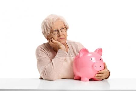 Photo for Pensive elderly woman with a piggybank seated at a table isolated on white background - Royalty Free Image