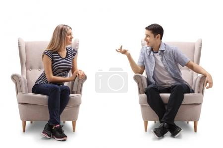 Photo for Young woman and a young man sitting in armchairs and talking isolated on white background - Royalty Free Image