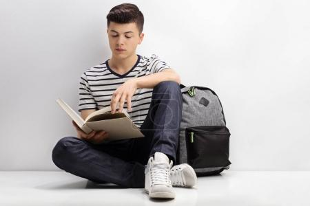 Teenage student reading a book