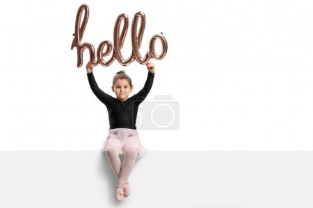ballerina sitting on a panel and holding a hello sign