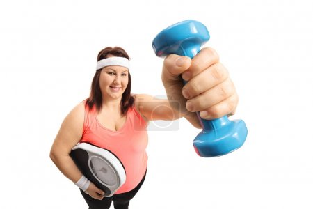 woman holding a weight scale and a dumbbell