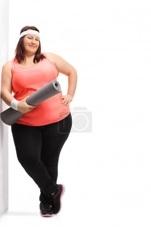 Overweight woman with an exercise mat