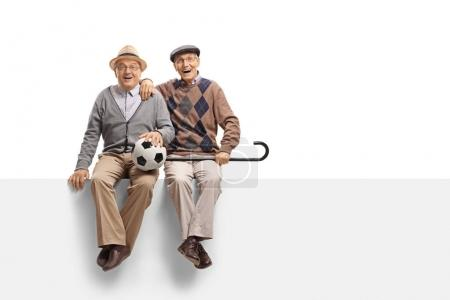 Joyful seniors with a football sitting on a panel