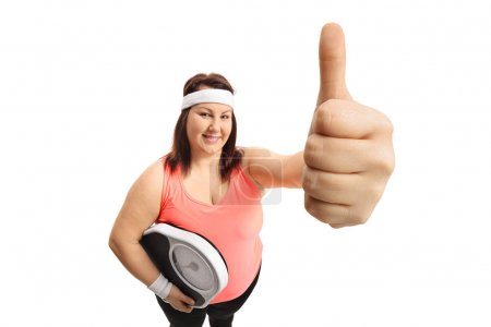 woman with a weight scale making a thumb up gesture