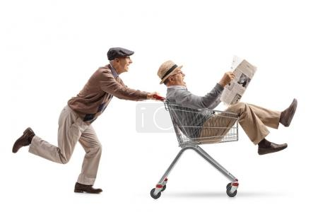 Senior pushing a shopping cart with another senior