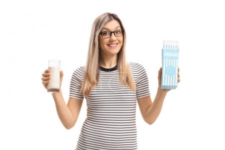 woman holding a glass of milk and a milk carton