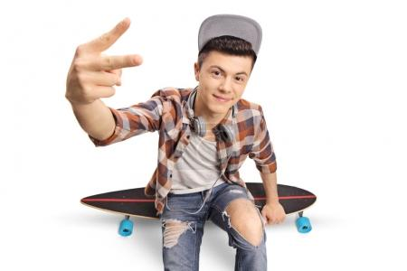 Photo for Teenage hipster sitting on a longboard and making a peace hand gesture isolated on white background - Royalty Free Image