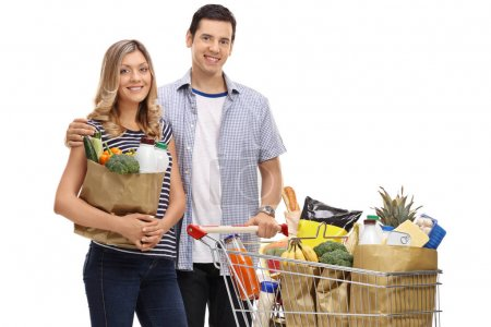 couple with shopping bags and a shopping cart with groceries