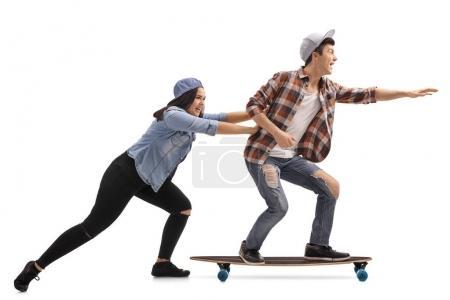 Photo pour Plan de profil complet d'une adolescente poussant un adolescent sur un longboard isolé sur fond blanc - image libre de droit
