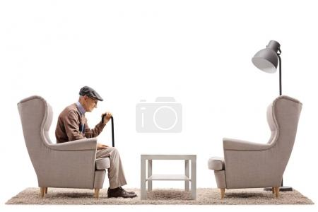 Lonely senior sitting in an armchair