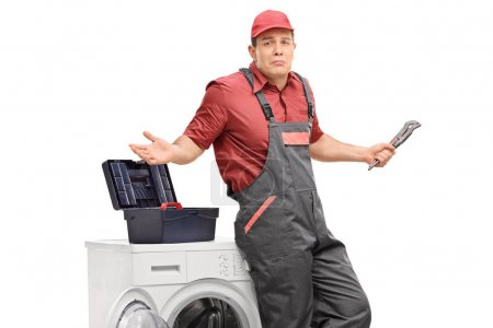 Uncertain repairman with a wrench against a washing machine