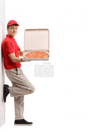 Photo for Full length portrait of a teenage pizza delivery boy leaning against a wall isolated on white background - Royalty Free Image