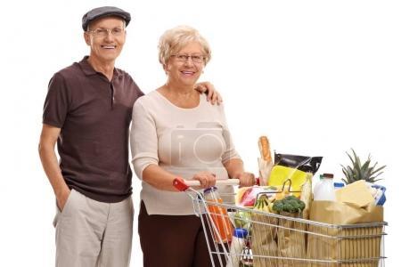 Photo pour Couple de personnes âgées avec un panier rempli d'épiceries isolées sur fond blanc - image libre de droit