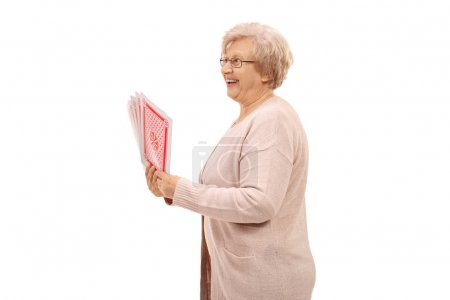 Cheerful elderly woman with playing cards