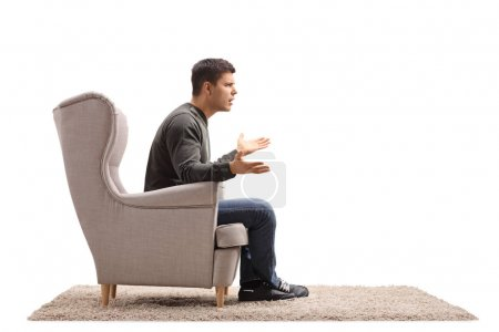 Young guy sitting in an armchair and arguing