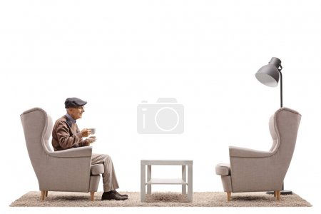 Photo pour Homme âgé avec une tasse assise dans un fauteuil isolé sur fond blanc - image libre de droit