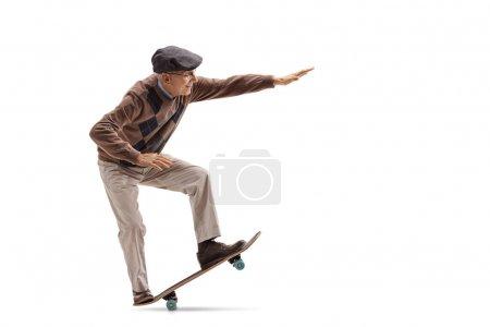 Photo pour Plan de profil complet d'une personne âgée chevauchant une planche à roulettes et faisant un manuel isolé sur fond blanc - image libre de droit
