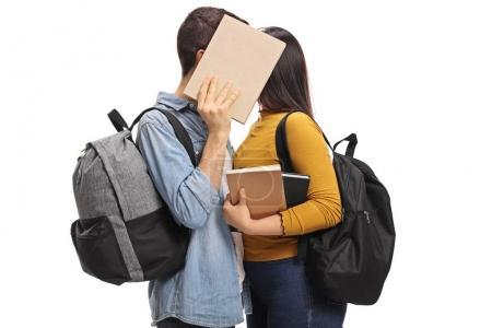 Photo pour Adolescents baisers derrière un livre isolé sur fond blanc - image libre de droit