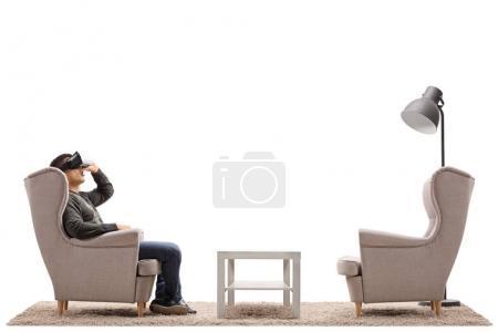 junger Mann, der virtuelle Realität durch ein vr-Headset erlebt, sitzt in einem Sessel auf weißem Hintergrund