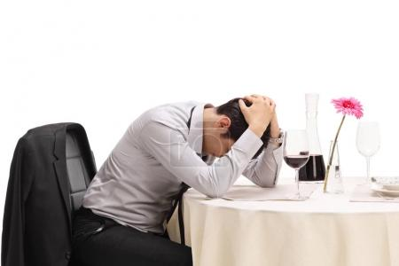Desperate man sitting alone at a restaurant table with his head down isolated on white background
