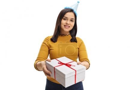 Photo pour Adolescente avec un chapeau de fête donnant un cadeau isolé sur fond blanc - image libre de droit