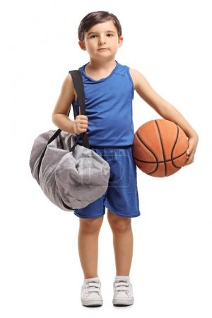 Full length portrait of a little basketball player holding a sports bag and a basketball isolated on white background