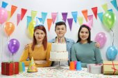 Teenagers with party hats and a birthday cake against a wall with decorations