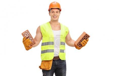 Construction worker holding bricks isolated on white background
