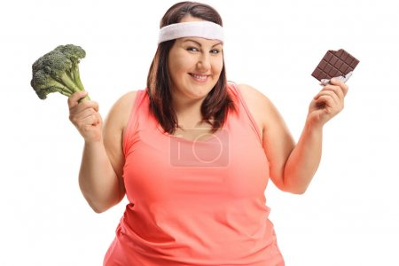 Overweight woman with broccoli and chocolate isolated on white background